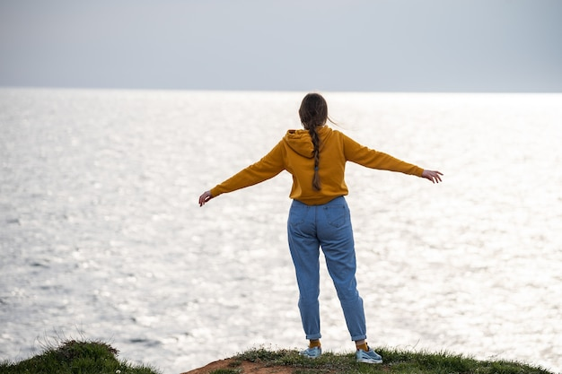 Une femme avec une longue tresse écarte les bras sur les côtés et admire le paysage marin magnifique vue mer f...