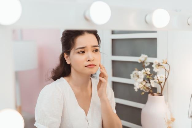 Femme look mirrior se sentir bouleversée et toucher son visage avec un problème d'acné