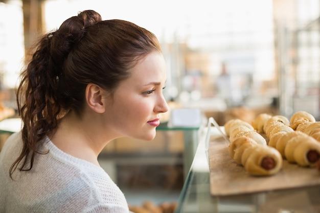 Femme lorgnant plateau de pastrys