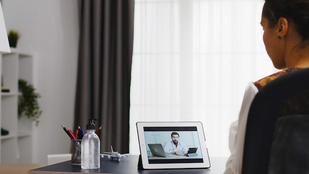 Femme lors d'un appel vidéo sur tablette avec son médecin assis au bureau.