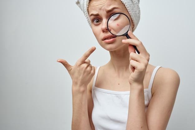 Femme avec une loupe en gros plan des problèmes de peau à la main