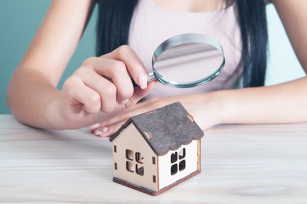 Une femme avec une loupe regarde la maison. concept de recherche à domicile