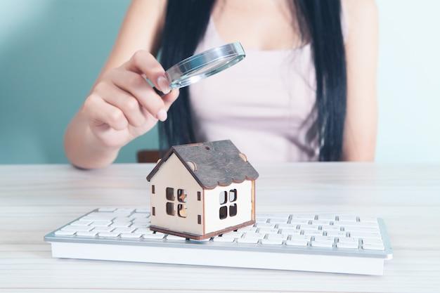 Une femme avec une loupe regarde la maison qui est sur le clavier. concept de recherche de maison en ligne