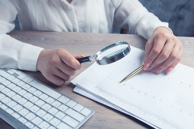 Femme avec une loupe regarde le papier sur le bureau