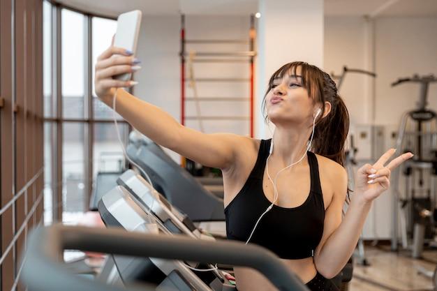 Femme ludique au gymnase prenant des selfies