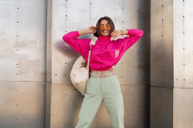 Femme ludique s'amusant en veste rose fluo sur mur urbain gris métallique