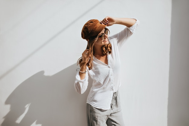 Femme lumineuse en casquette, chemisier léger et pantalon gris portait des lunettes de soleil et posant sur un espace blanc.