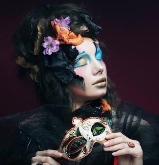 Femme avec lumineux maquillage avec masque de carnaval