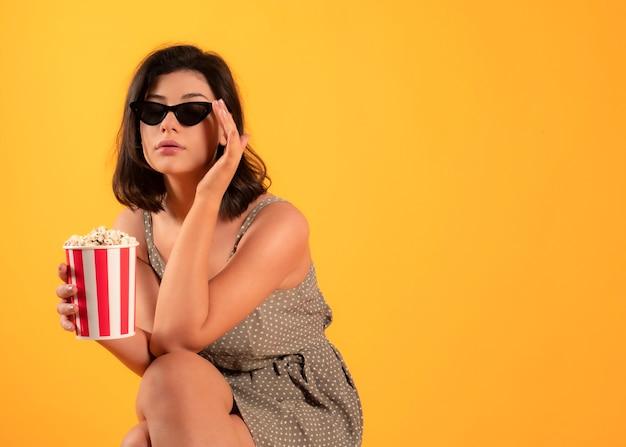 Femme avec des lunettes 3d et du pop-corn allant au concept de cinéma