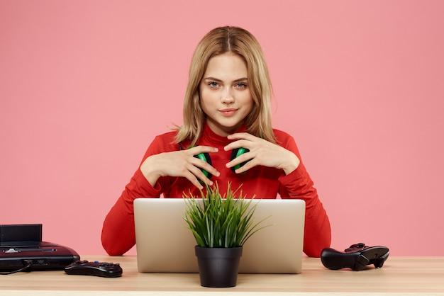 Une femme à lunettes 3d joue à un jeu d'ordinateur dans des consoles avec des joysticks dans les écouteurs avec un ordinateur portable