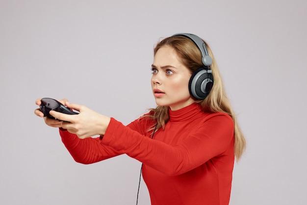 Une femme à lunettes 3d joue à un jeu d'ordinateur dans des consoles avec des joysticks dans les écouteurs