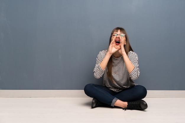 Femme à lunettes assise sur le sol en train de crier et d'annoncer quelque chose