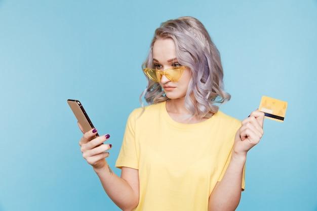 Femme à lunettes avec carte de crédit et mobile isolé sur salle bleue.