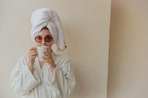 Une femme avec des lunettes dans un peignoir et une serviette à l'hôtel boit du café dans une tasse blanche. photographie joyeuse de style de vie