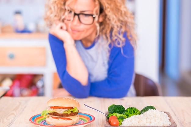 Une femme avec des lunettes doit choisir des légumes ou un hamburger - à la maison à l'intérieur - sur la table - mode de vie et concept sains