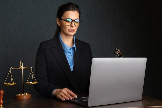 Femme à lunettes élégantes écrit notaire dans le manuel au cours de l'apprentissage en ligne sur ordinateur portable, assis à l'intérieur du restaurant. coordinateur marketing féminin à l'aide de journal pour le travail