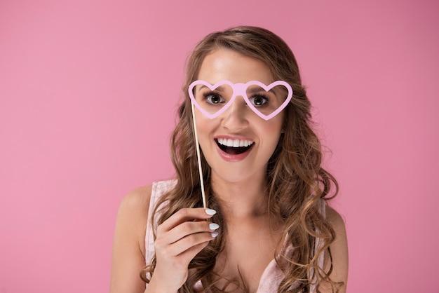 Femme avec des lunettes en forme de coeur