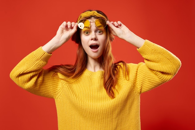 Femme à lunettes jaunes avec un bandage sur la tête pull jaune hipster fond rouge
