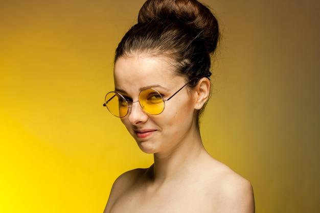 Femme à lunettes jaunes, épaules nues, gestes avec les mains. photo de haute qualité