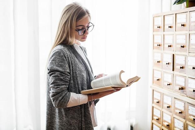 Femme à lunettes lisant près de la fenêtre