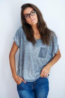 Femme avec des lunettes et les mains dans les poches