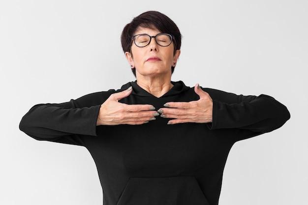 Femme avec des lunettes méditant à l'intérieur