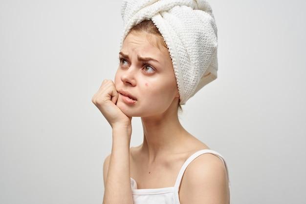 Femme avec des lunettes montre un doigt sur un bouton rouge sur son visage problèmes de santé acné