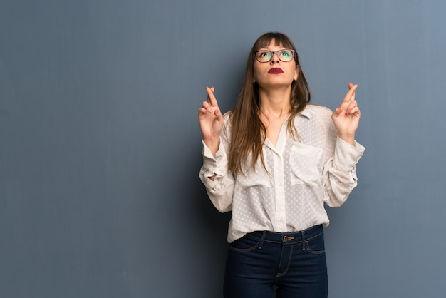 Femme avec des lunettes sur un mur bleu avec les doigts qui se croisent et souhaitant le meilleur