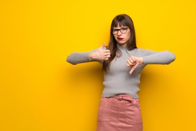 Femme, lunettes, mur jaune, signe bon-mauvais indécis entre oui ou non
