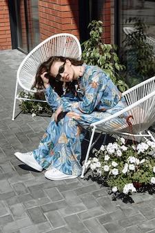 Femme à lunettes posant assis sur une chaise dans un nouveau catalogue de vêtements de collection