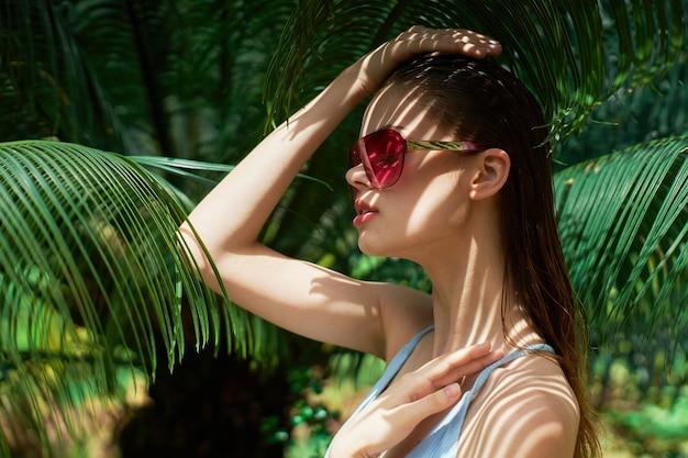 Une femme avec des lunettes près des feuilles vertes d'un palmier tient sa main sur sa tête. photo de haute qualité