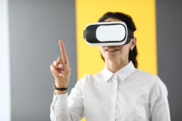 Femme à lunettes de réalité virtuelle se lève et tient ses pouces vers le haut.