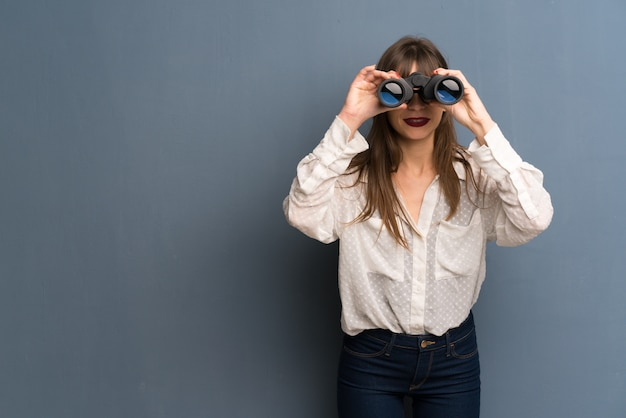 Femme à lunettes et regardant au loin avec des jumelles