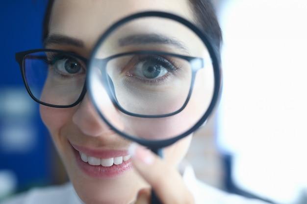 Femme à lunettes regarde à travers la loupe et sourit.