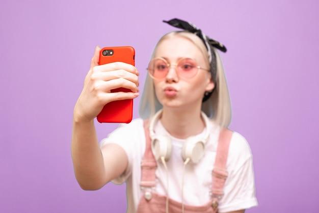 Femme à lunettes rose vif prend selfie sur smartphone avec grimace