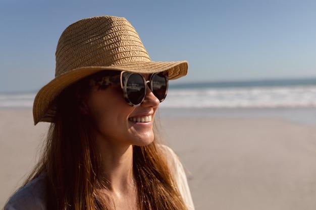 Femme à lunettes de soleil et chapeau se détendre sur la plage