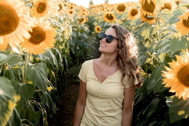 Femme avec des lunettes de soleil dans le champ de tournesol