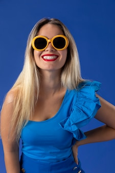 Femme avec des lunettes de soleil jaune coup moyen