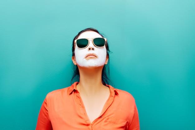 Femme avec des lunettes de soleil masque de beauté blanc sur fond turquoise