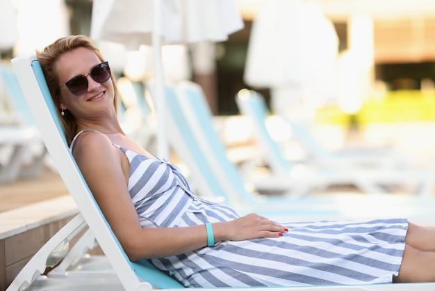 Femme à lunettes de soleil et robe se trouvent sur une chaise longue sur la plage et les bains de soleil.