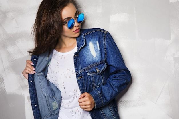 Femme à lunettes de soleil rondes posant près d'un mur gris