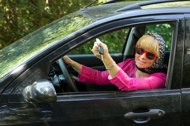 Femme en lunettes de soleil roses et rouges dans la voiture