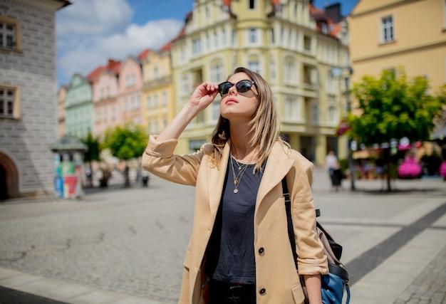 Femme à lunettes de soleil et sac à dos à la place du centre-ville âgé. pologne