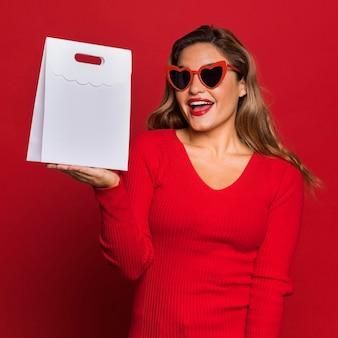 Femme avec des lunettes de soleil et un sac en papier