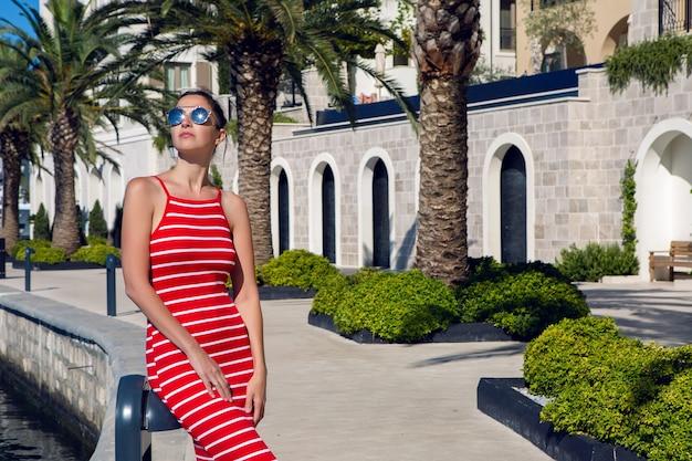 Femme avec des lunettes de soleil se dresse sur la jetée parmi les palmiers