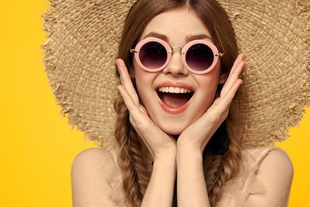 Femme avec des lunettes de soleil tresses chapeau de paille portrait agrandi amusement émotion