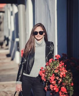 Femme à lunettes de soleil et veste en cuir