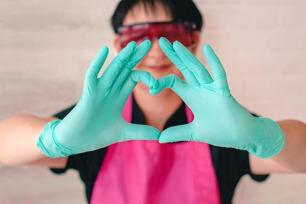 Femme à lunettes tablier gants en caoutchouc montrant signe amour par ses doigts santé