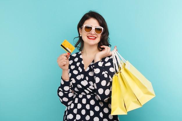 Femme à lunettes tenant une carte et des sacs sur le fond bleu.