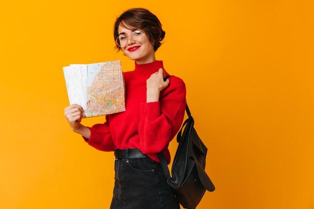 Femme à lunettes tenant le plan de la ville